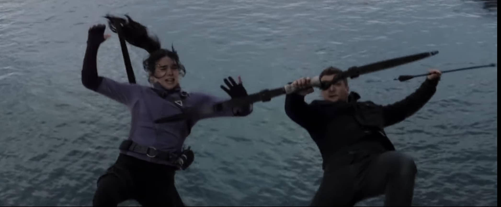 Kate Bishop and Clint Barton falling towards a body of water while getting ready to show an arrow up at the sky.
